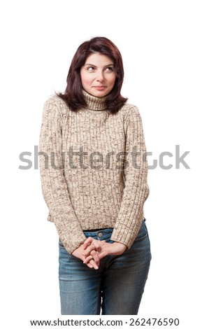 A nice young girl in sweater and jeans thoughtfully looks up on isolated white background - stock photo