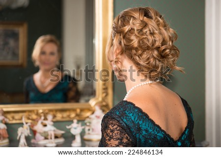 A nice young woman is seen from back while she's looking at herself at the mirror. She is elegantly dressed and wearing a pearls necklace.  - stock photo