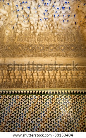 A niche in the Alhambra palace in Granada, showing stalactite vaulting, arabic stucco inscriptions and patterned tiling - stock photo