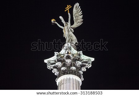 A night-time view of the sculpture on top of the column at Heroes Square in Budapest.