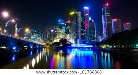 A night view of the city, with skyscrapers downtown and the bridge, which is reflected on the water surface (Singapore) - stock photo