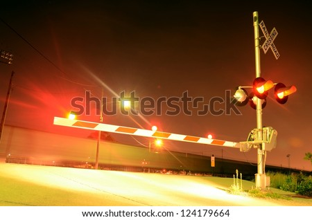 A night view of the gates at a railroad crossing. Lights a flashing and a blurred train is moving in the background. - stock photo