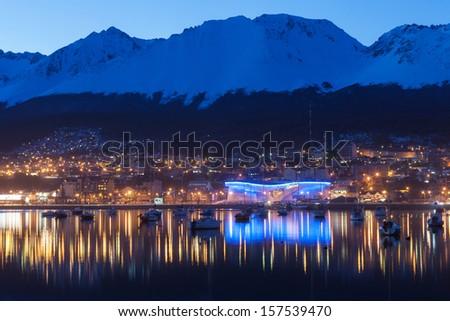 A night view of Ushuaia, Tierra del Fuego. Boats line the harbor - stock photo