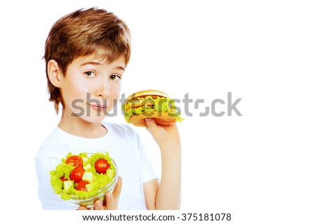 A nine year old boy making choice between fast food burger and fresh vegetable salad. Fast food. Concept of healthy and unhealthy food. Isolated over white. - stock photo