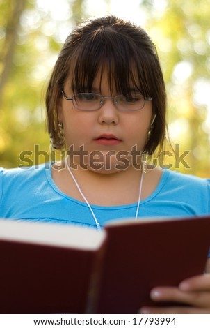 A nine year old girl studying from her text book for school