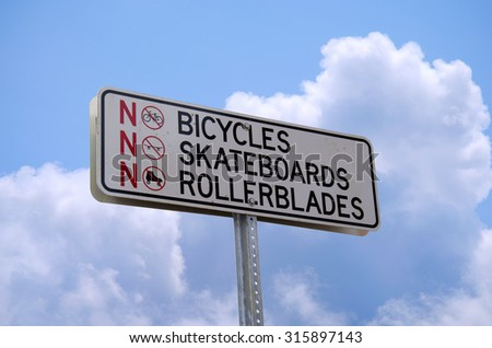 "A ""NO BICYCLES NO SKATEBOARDS NOT ROLLERBLADES"" sign with a sky background. An OUTLINE PATH IS INCLUDED so the sign can be dropped into any setting very easily."