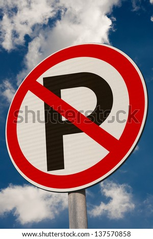 A 'No Parking' sign against a  blue sky. - stock photo