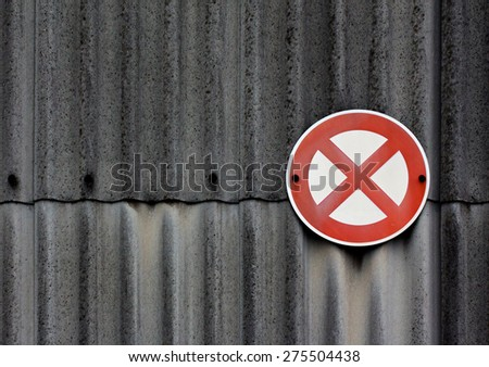 A no stopping sign on asbestos wall - stock photo