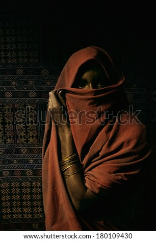 A north African woman covers her face with a veil. She is wearing wrist bangles and standing in front of a kilim rug. Morocco, Africa. / Veiled African woman Scanned from film. - stock photo