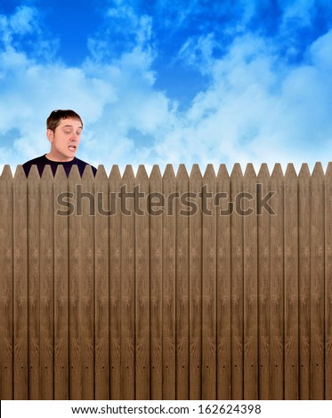 A nosy neighbor is looking over a fence in a backyard at something with shock and surprise on his face for a secret or privacy concept. - stock photo