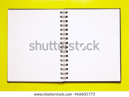 A note book open on a plain page, on a bright yellow background