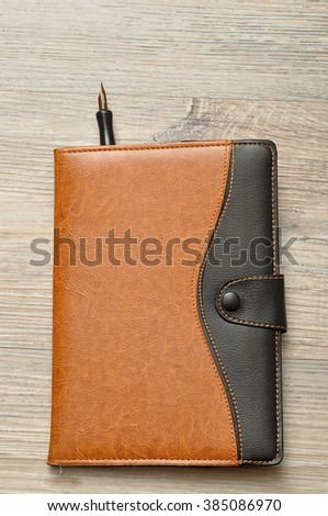 A note book with a fountain pen displayed on a table - stock photo