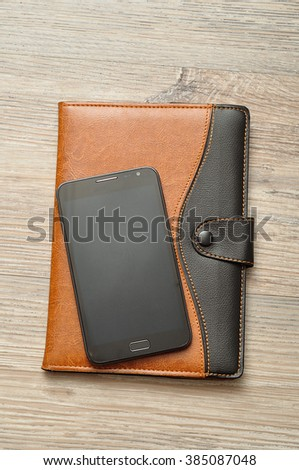 A notebook displayed with a smart phone on a wooden table - stock photo