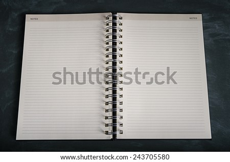 A notebook opened to a blank page lays on a desk - stock photo