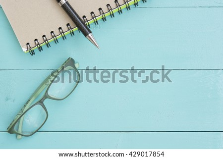 A notebook,pen and glasses on the green table,Top view with copy space
