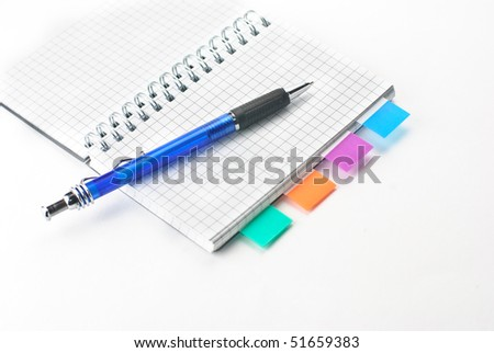 A notepad with a pen isolated on a white background