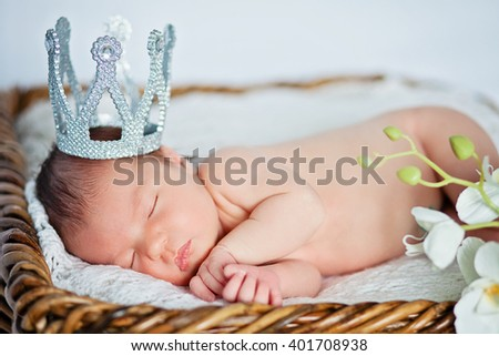 A nude newborn baby girl wearing a crown and asleep in basket on a white textured blanket, white lily in the background - stock photo