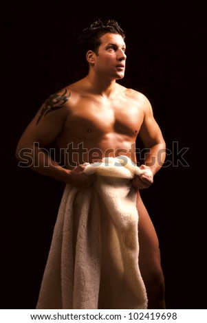 A nude young man covering himself with a towel - stock photo
