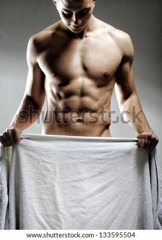 A nude young man covering himself with a towel  as copy space - stock photo