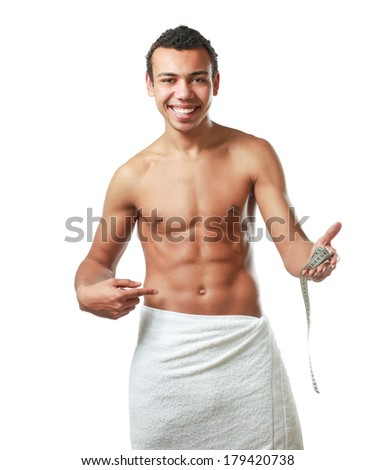 A nude young man covering himself with a towel with tape measuring - stock photo