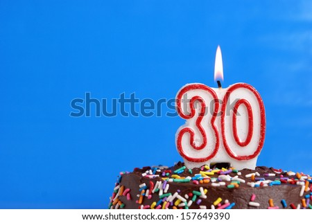 A number candle is lit in celebration of thirty years. - stock photo