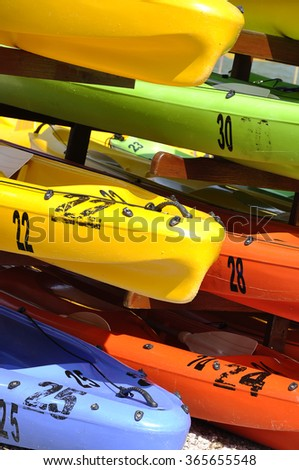 A number of colored plastic rowing boats docked - stock photo