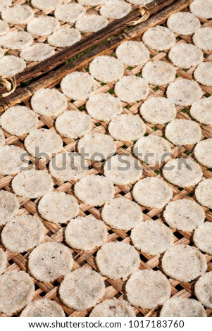 A number of compressed rice cakes or galettes on a rack outside drying under the sun