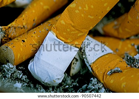 A number of fag ends in a ash tray - stock photo