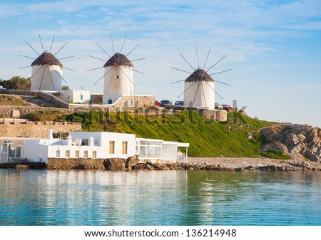 A number of mills on the hill near the sea on clouds on the island of Mykonos in Greece - stock photo