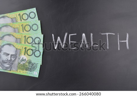 A number of one hundred Australian dollar notes on a blackboard where Wealth is handwritten in white chalk - stock photo