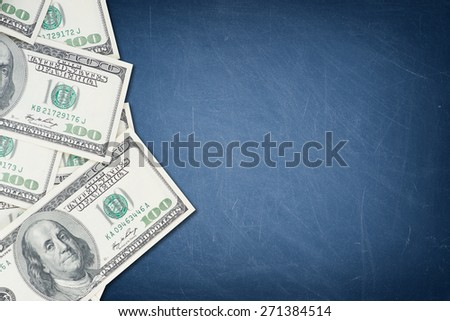 A number of one hundred US dollar notes on a blue chalkboard - stock photo
