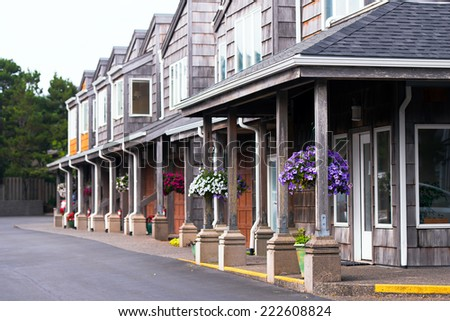 A number of two-storey wooden houses with a portico on columns and gabled roofs and walls, chipped cedar siding. On pillars portico hung baskets with colorful small flowers that create a unique. - stock photo