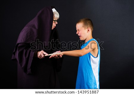 A nun hitting a boy in the knuckles with a ruler