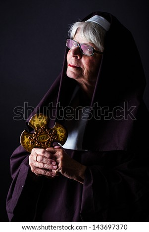 A nun holding a cross and looking up - stock photo