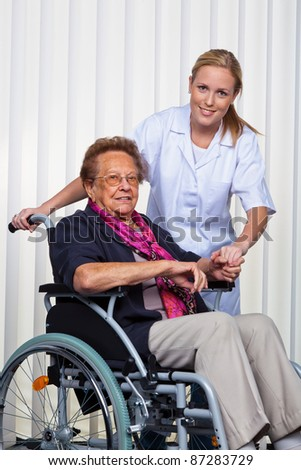 a nurse and an old woman in a wheelchair.