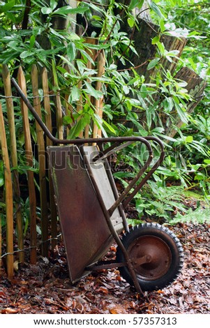A old rusty wheel-barrow standing by a fench. - stock photo