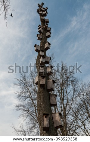 A old tree with many hand made birdhouses - stock photo