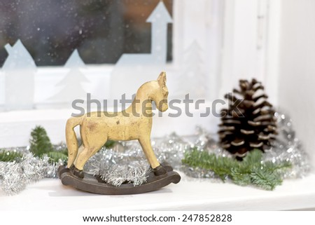 a old wooden rocking horse with christmas decoration on a window sill - stock photo