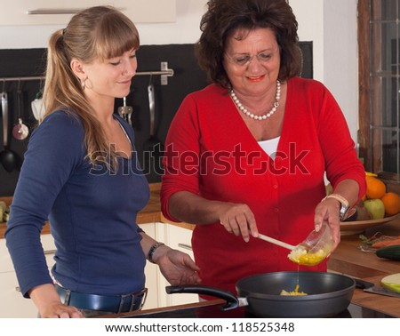 A older and a younger women are cooking in the kitchen - stock photo