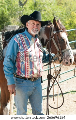 A older man in a black cowboy hat holds the bridle of a pinto horse. - stock photo