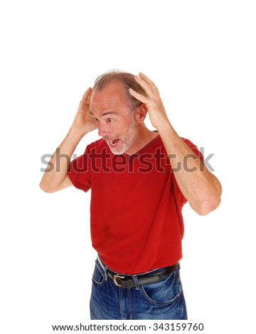 A older man in a red t-shirt and jeans standing with his hands on his head