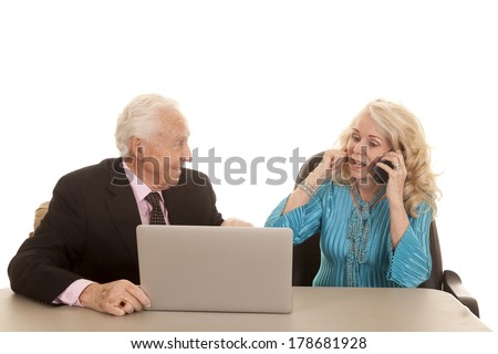 a older man working on the computer while the older woman is plugging her ear so she can talk on the phone. - stock photo