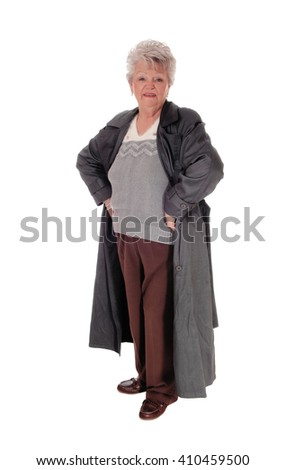 A older senior citizen woman standing isolated for white backgroundin a dark gray coat with her hands on the hips. - stock photo