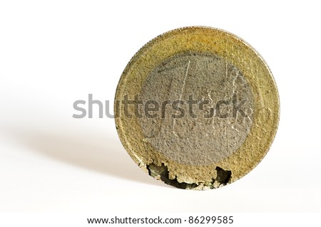 A one euro coin crumbles under the strain of the economic crisis. - stock photo