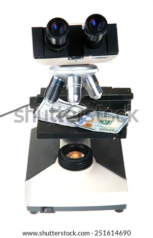 a one hundred dollar bill set up for examination under a microscope to view if it is counterfeit or legitimate. isolated on white with room for your text