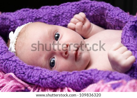 A one month old new born rests happily in her blanket.