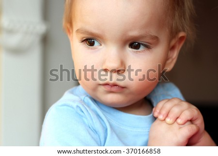 A one year blond boy looking aside musingly and thoughtfully and putting his hands together in pray, close-up emotional portrait, indoor  - stock photo