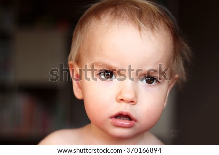 A one year blond boy looking aside musingly and thoughtfully, close-up emotional portrait, indoor  - stock photo