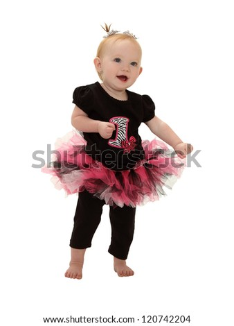 A one year old baby dances a happy dance in her tutu isolated on white