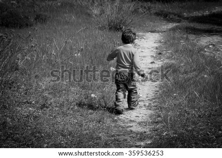 A one year old boy taking some of his first steps outdoors on a path.Vintage style photo with vignette